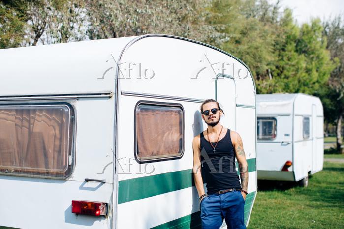 Man leaning against caravan