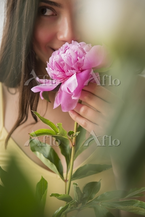 Hispanic woman smelling pink f・・・