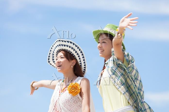 青空の下で腕を広げる日本人女性