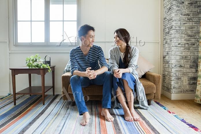 ソファーで過ごす若い夫婦